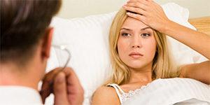 женщина лежит больная в постели и рядом врач