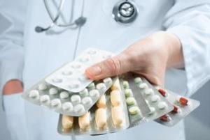 доктор держит в руках пачки таблеток
