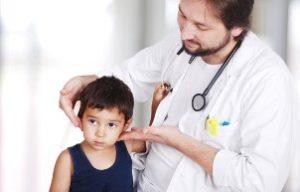 врач осматривает шейные лимфоузлы у ребёнка