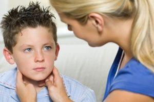 врач осматривает у мальчика околоушные слюнные железы