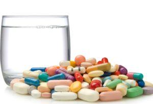 куча таблеток и стакан воды