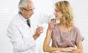 врач делает девушке прививку