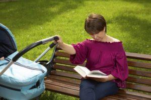молодая мама сидит на лавочке и качает коляску