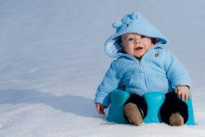 малыш на улице играет в снегу