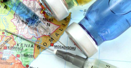 шприц и вакцина поверх карты Африки