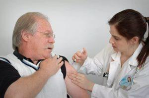 врач делает прививку пожилому человеку