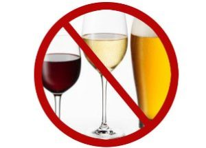 знак stop поверх бокалов с алкоголем