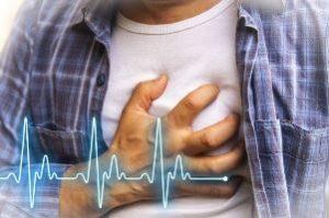 человек держится за грудь в районе сердца на фоне кардиограммы