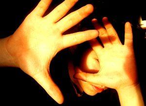 человек закрывает лицо руками от света