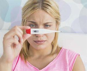 женщина смотрит на термометр