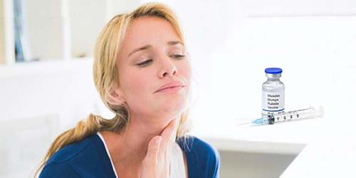 у женщины боль в горле, рядом лежит вакцина и шприц