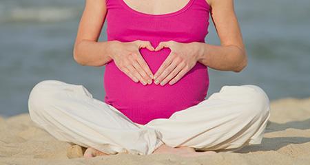 беременная женщина сидит на пляже