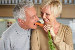 пожилой мужчина ест морковку