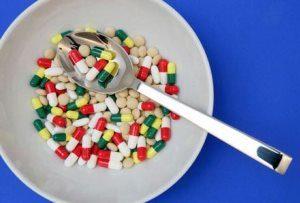 много лекарств в тарелке с ложкой
