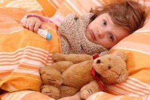 мальчик с перевязанным горлом лежит в постели