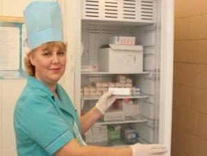 врач достаёт вакцину из холодильника