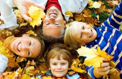 родители с детьми лежат в осенней листве