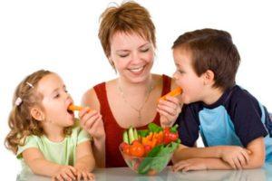мама кормит детей овощами