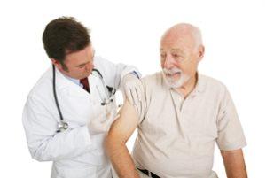 доктор делает прививку пожилому мужчине