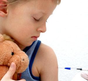 мальчику делают прививку в руку
