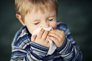 мальчик чихает в носовой платок