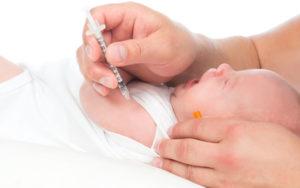 новорожденному ребёнку делают прививку в руку