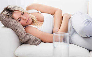 женщина лежит держась за живот на фоне стакана с водой