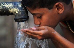 мальчик пьёт воду из под колонки