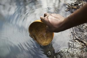 человек набирает воду из открытого водного источника